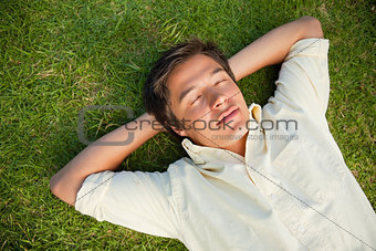 Man lying with his eyes closed and both hands behind his neck