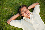 Man smiling as he lies with both hands behind his neck