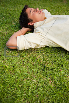 Man lying in grass with his eyes closed and both hands behind hi