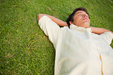 Man lying in grass with his eyes closed and his head resting on