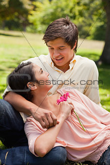 Woman holding a flower while lying against her friend who is loo