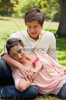 Man smiling as he looks down at his friend who is resting agains