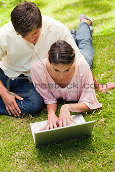 Two friends looking into a laptop together while lying down