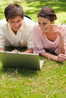 Two friends using a laptop together while lying down