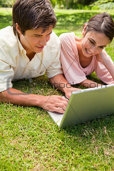 Two friends smiling as they use a laptop together