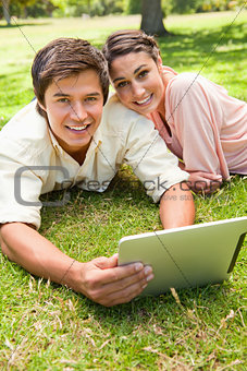 Two friends looking ahead as they use a tablet together