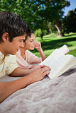 Two friends reading books while lying in a park