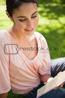 Woman smiling while reading a book as she sits on grass
