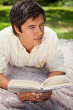 Man looking to his side while reading a book as he lies on a bla