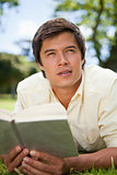 Man looks to the distance while reading a book as he is lying do
