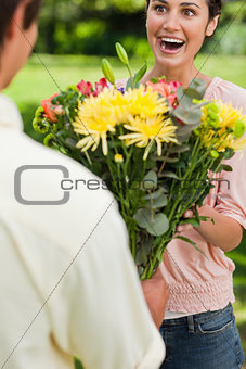 Woman surprised as she is presented with flowers by her friend