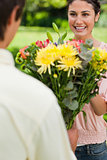 Woman smiling as she is presented with flowers by her friend
