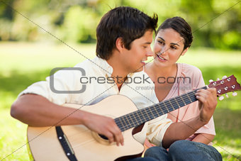 Man playing the guitar while his friend watches him