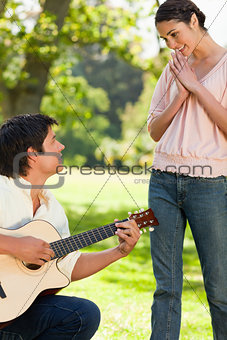 Woman standing in admiration of her friend who is playing the gu