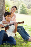 Woman holding her friend as her plays the guitar