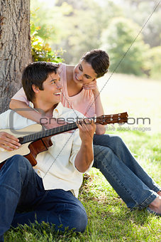 Woman looking at her friend while holding him as her plays the g