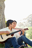 Man playing a guitar and sitting against a tree while his friend
