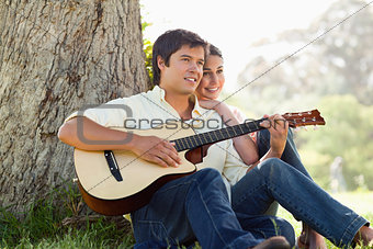Man playing the guitar while looking into the distance with his