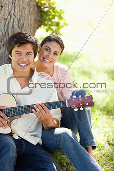 Woman smiling with her friend who is holding a guitar