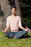 Woman sitting in a yoga position near a tree