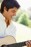 Man smiling as he plays a guitar