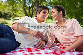 Two friends looking at each other while holding glasses during a