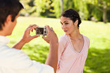 Man takes a photo of his friend while she poses