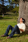 Man using headphones to sing along to music while resting a tree