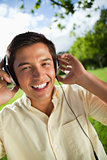 Man smiling while using headphones to listen to music in a park
