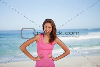 Young woman sunbathing while standing with hands on hips