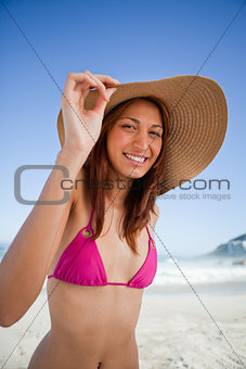 Young smiling woman holding her hat brim while wearing a pink sw