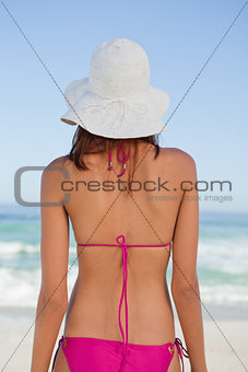 Back view of a teenager looking at the sea