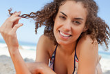 Smiling young woman holding a lock of hair with her fingers