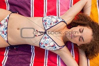 Overhead view of a beautiful woman napping on her colourful beac