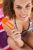 Young attractive woman in bikini holding an ice lolly while look