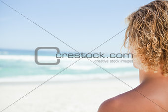 Young blonde man looking at the sea while sunbathing