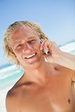Smiling blonde man looking at the camera while calling with his