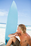 Serious blonde man sitting on the beach with his surfboard next