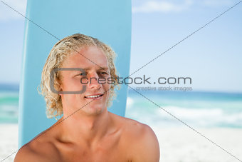 Smiling young man sitting on the beach with his surfboard