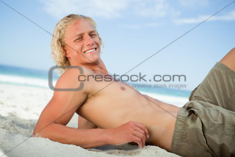 Smiling blonde man lying on the beach while sunbathing