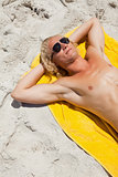 Overhead view of a blonde man lying on his beach towel