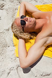 Young blonde man wearing sunglasses while lying on his yellow be
