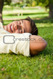 Man smiling while lying with the side of his head resting on his