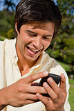 Close-up of a man using a phone while he is sitting down