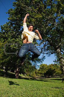 Man looking down to the ground as he jumps with his arms raised