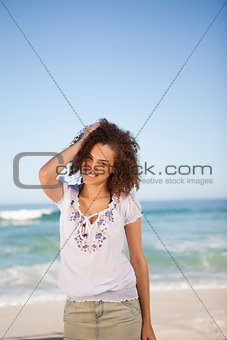 Young woman standing in front of the sea with hand on her head