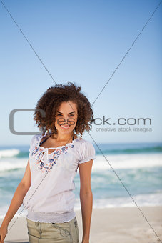 Young smiling woman standing on the beach