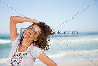 Young woman closing her eyes while standing on the beach
