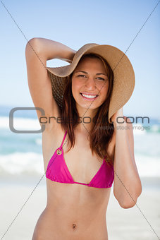 Smiling teenager girl holding her hat with her hands