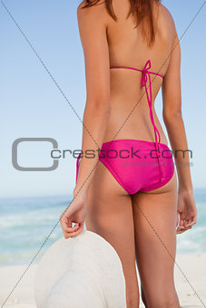 Back view of a young woman body in front of the sea